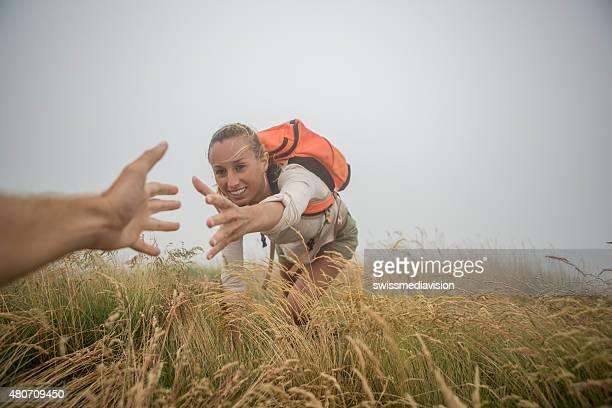 Wanderer Ziehen Sie sich beim mountain top um Hilfe bitten