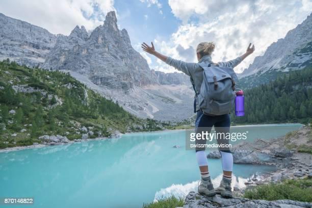 Hiker reaching mountain top, Dolomites, Italy