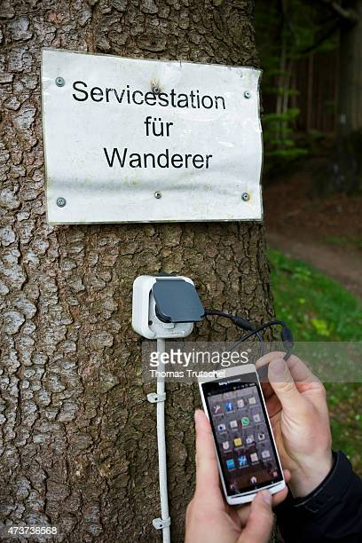 Hiker recharging his mobile phone at an outlet that is attached to a tree along a hiking trail on May 07 2015 in Masserberg Germany Mobile Phone...
