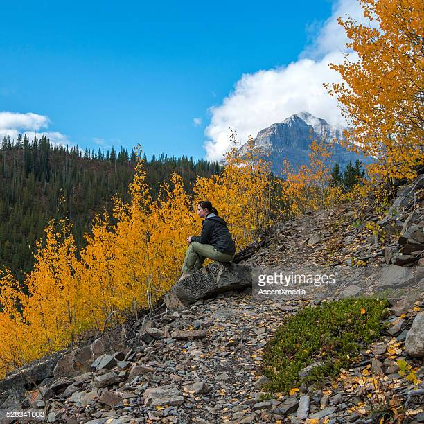 Hiker relaxes on rock in mountain forest, autumn