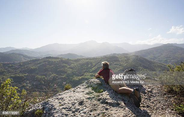 Hiker relaxes on rocky bluff, looks out to hills