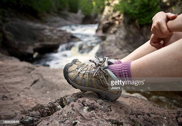 Hiker relaxing in boulders by a water creek