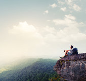 Hiker relaxing on the rock with a backpack