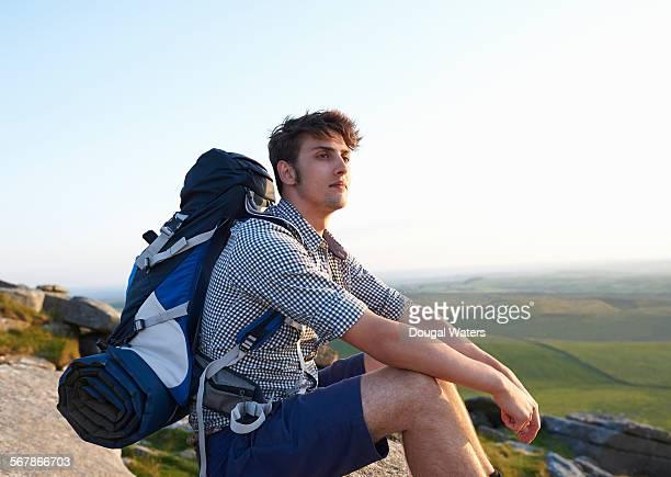 Hiker resting on rocky hilltop.