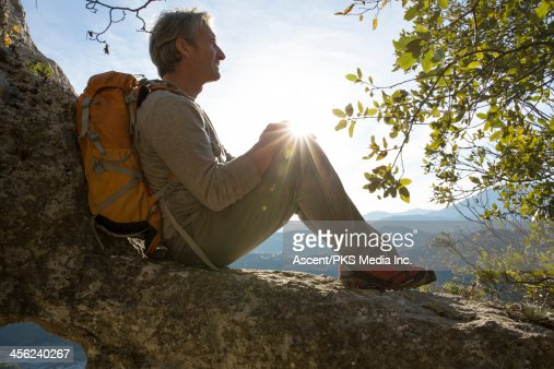 Hiker rests against rocks near tree, valley below : Stock Photo