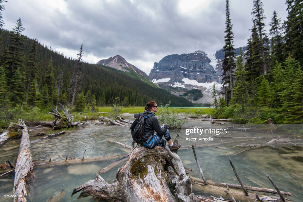 Hiker rests on log in mountain stream