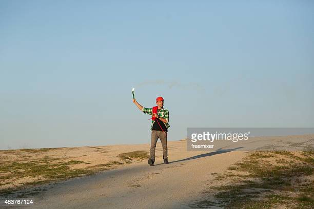Hiker running with torch on dirt road