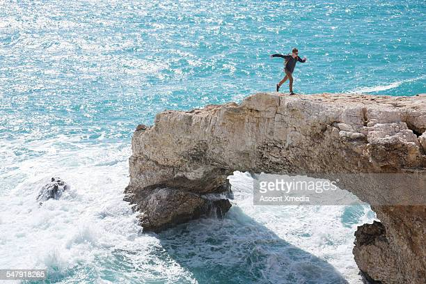 Hiker runs along crest of natural rock bridge