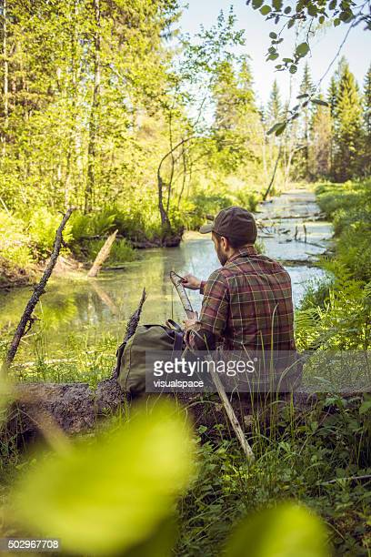 Wanderer schärfen Einen Wanderstock nahe gelegenen Wald Fluss