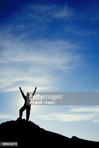 woman silhouetted on pinnacle, arms raised high into the sky