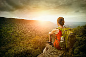 Young woman hiker sits on the edge of the cliff and enjoying sunrise looking at the valley and mountains. Traveling along Asia, active lifestyle concept