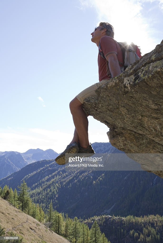 Hiker sits on rock overhang above mtns, valley : Stock Photo