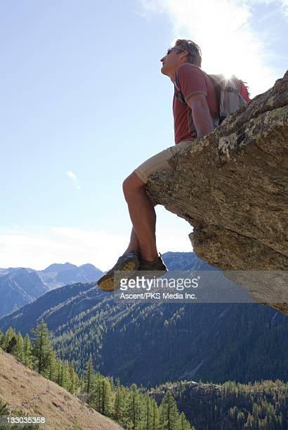 Hiker sits on rock overhang above mtns, valley