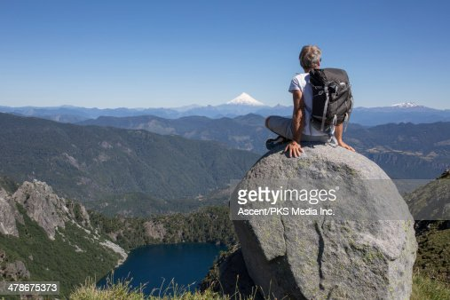 Hiker sits on rock perched above valley, looks off