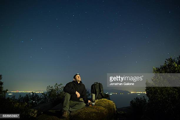 Hiker sits watching the stars
