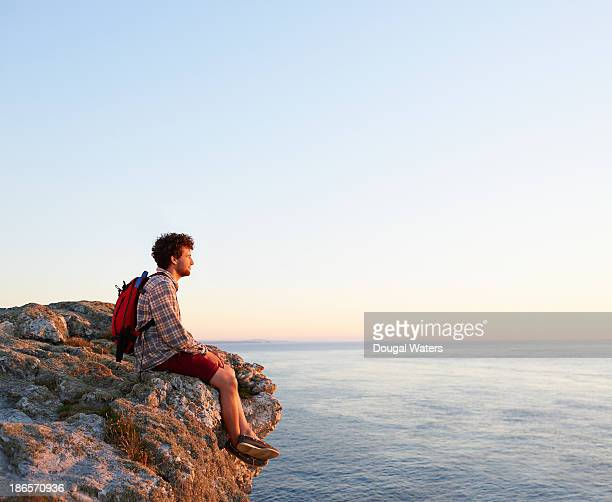Hiker sitting on coastal rock looking out to sea.