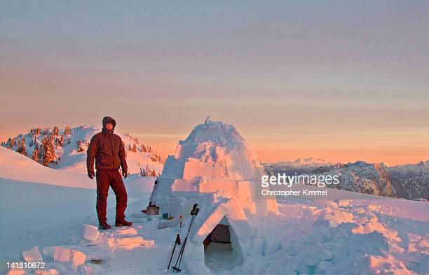 Hiker standing beside his igloo at sunrise