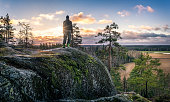 Hiker standing front of beautiful landscape at early morning in Jaanankallio, Hyvinkää, Finland
