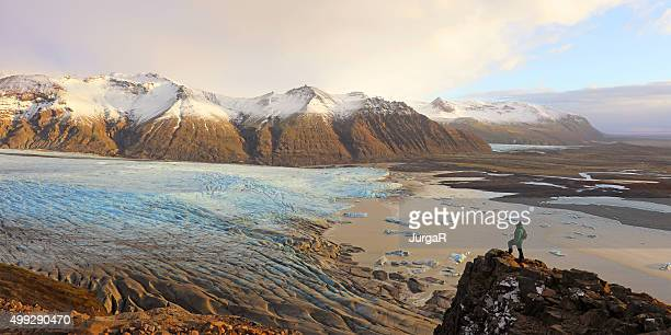 De caminhada de pé em um Penhasco com vista para Glaciar de Skaftafell na Islândia
