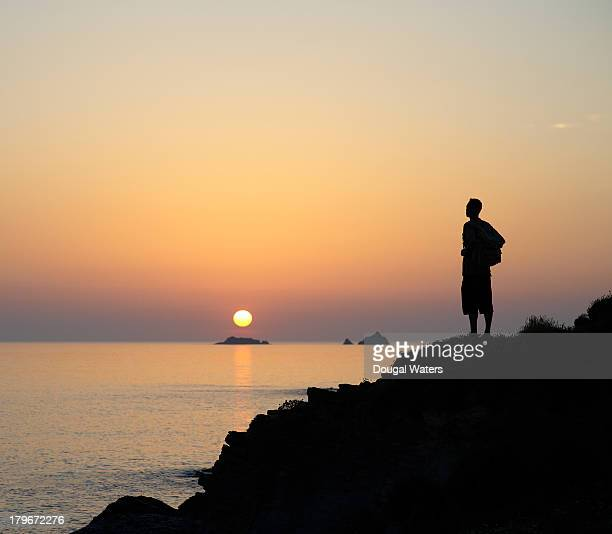 Hiker standing on coastline at sunset.