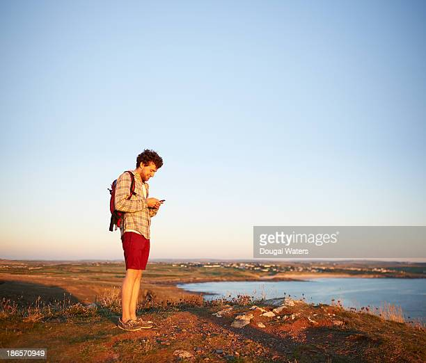 Hiker standing on coastline using mobile phone.