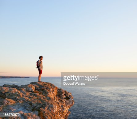 Hiker standing on rock and looking out to sea.