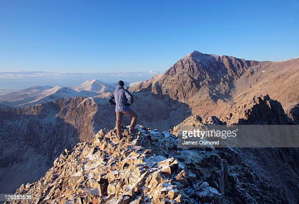 Hiker standing on the Crib Goch knife-edge ridge, 923 metres above sea level within the Snowdon Horseshoe, looking towards Mount Snowdon and admiring a breathtaking view across the rugged lansdscape of Snowdonia National Park
