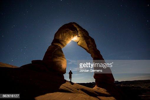 A hiker standing underneath an arch.