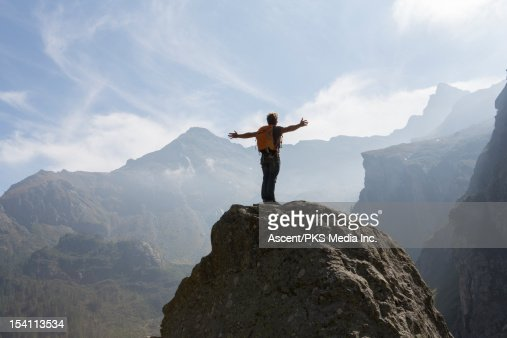 Hiker stands on boulder, arms outstrecthed : Stock Photo