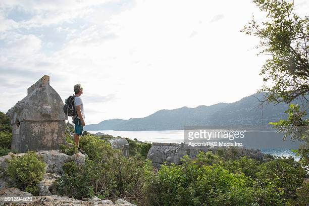Hiker stands on knoll beside sarcophagus,looks out