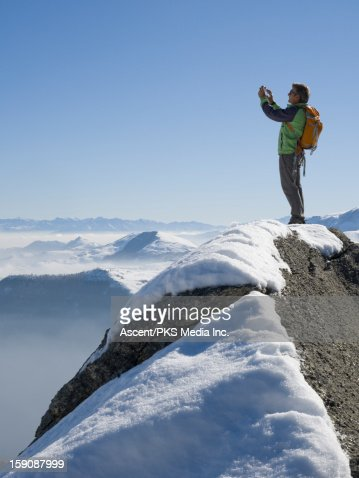 Hiker stands on mountain summit, takes picture : Stock Photo