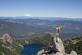 Hiker stands on rock above valley, arms outstretch