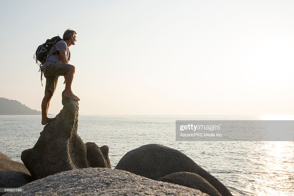 Hiker stands on rock crest, looks out to sea : Stock Photo