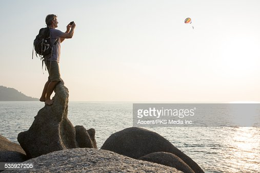 Hiker stands on rock crest, takes pic of parasail : Stock Photo