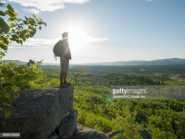 Hiker stands on valley overview, looking off