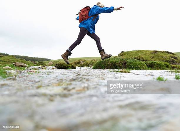 Hiker stepping across stream in countryside