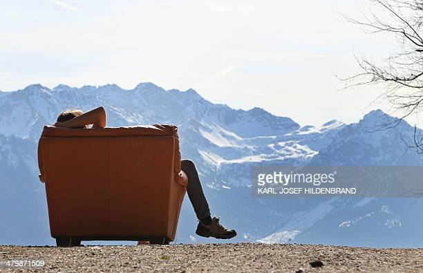 A hiker takes a rest in an armchair near the Hochbichl alpine hut near Ofterschwang southern Germany on March 21 2014 AFP PHOTO / DPA / KARLJOSEF...