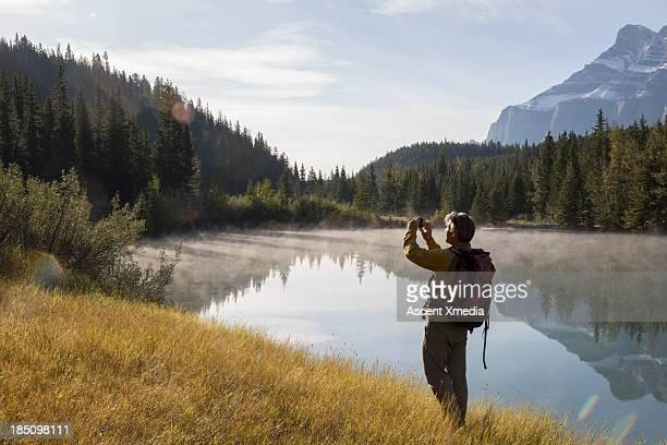 Hiker takes pic with samrt phone, above mtn lake