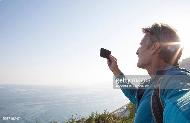 Hiker takes pic with smart phone above sea