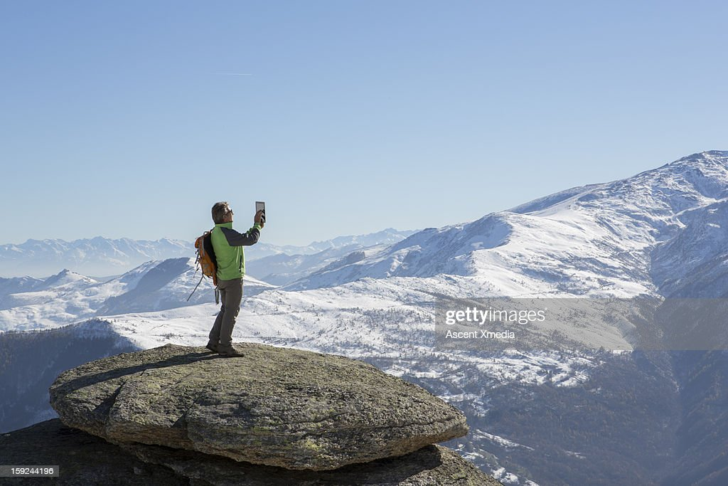 Hiker takes picture with digital tablet, on ummit : Stock Photo
