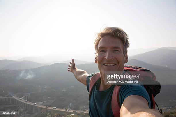 Hiker takes selfie portrait on mountain top
