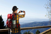 Hiker taking photograph of mountains, Montseny, Barcelona, Catalonia, Spain