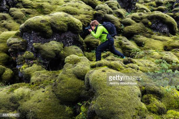 Hiker taking photograph on mossy rock formations