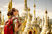 Hiker traveling  with backpack and looks at Buddhist stupas. Myanmar