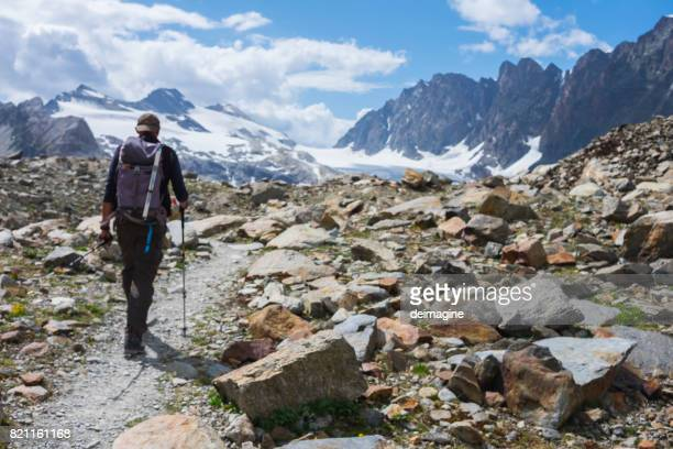 Hiker trekking on high mountain path