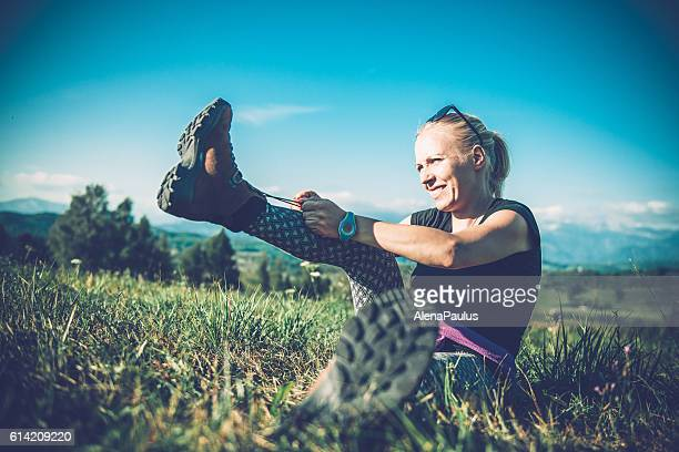 Hiker tying her shoe in the mountains, Europe