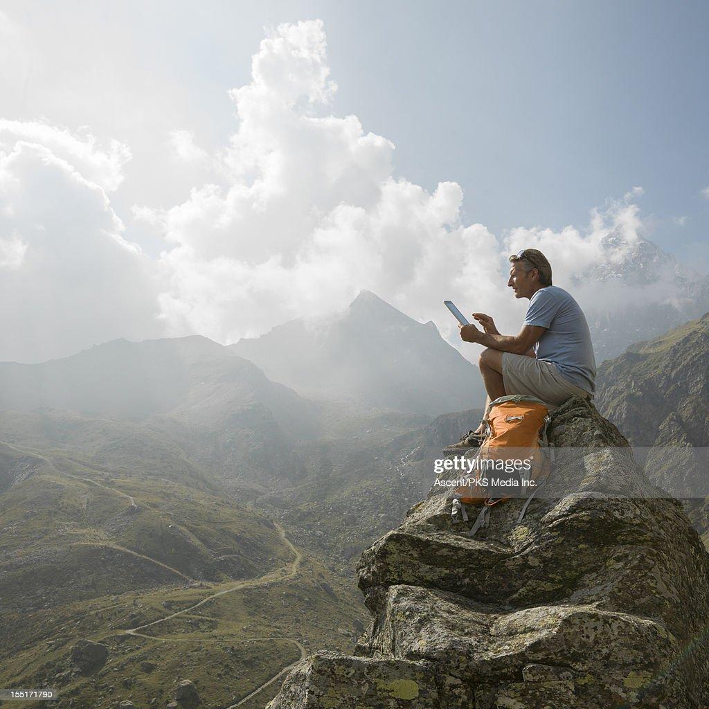 Hiker uses digital tablet on pinnacle summit, mtns : Stock Photo