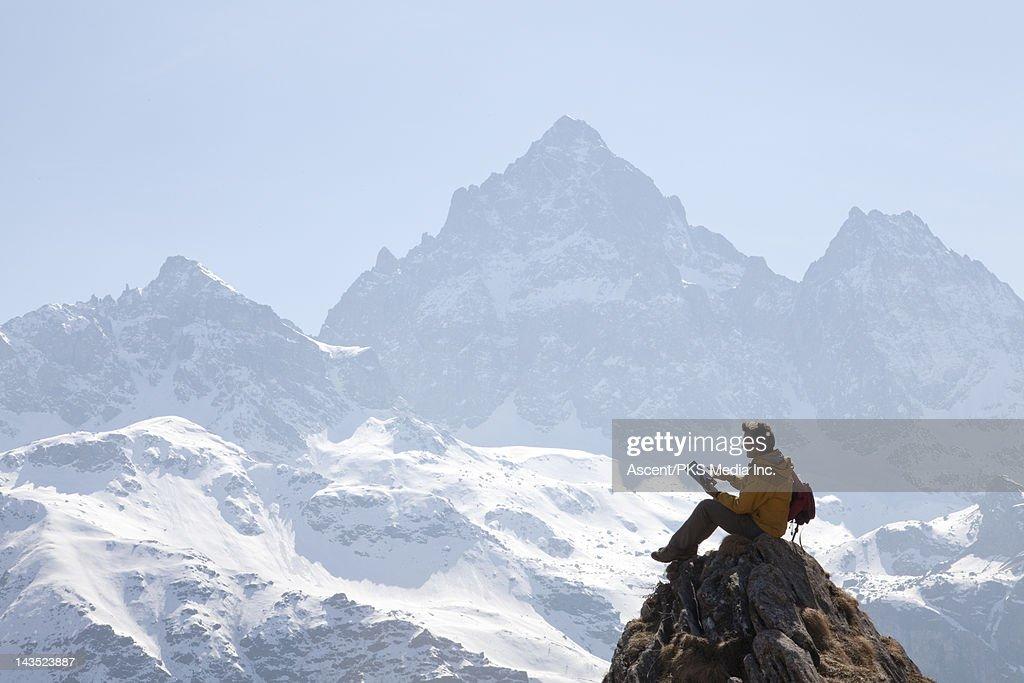 Hiker uses digital tablet on ridge crest, mtns : Stock Photo