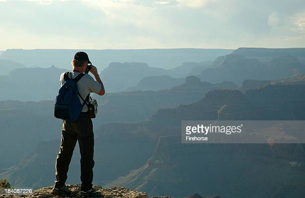 Hiker using binoculars to view canyon