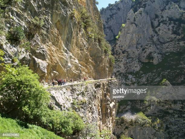 Hiker walking a path through some high cliffs